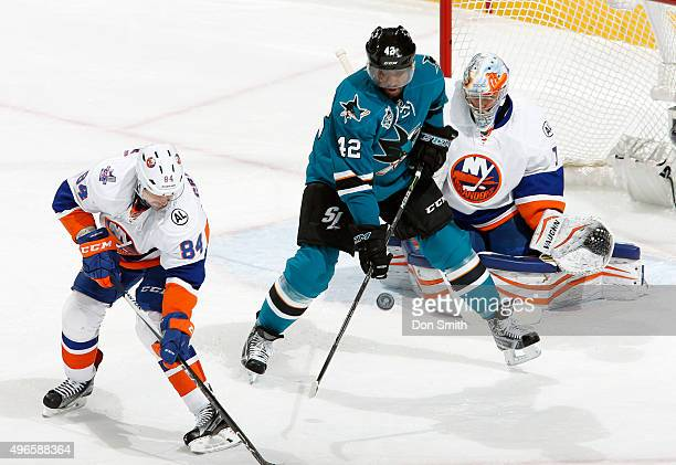 Joel Ward of the San Jose Sharks gets a stick on the puck against Mikhail Grabovski and Thomas Greiss of the New York Islanders during a NHL game at...