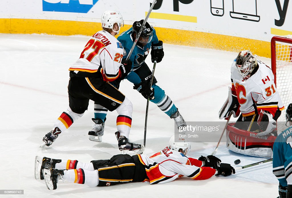 Joel Ward #42 of the San Jose Sharks has his shot blocked against Kris Russell #4, Dougie Hamilton #27, and Karri Ramo #31 of the Calgary Flames during a NHL game at the SAP Center at San Jose on February 11, 2016 in San Jose, California.
