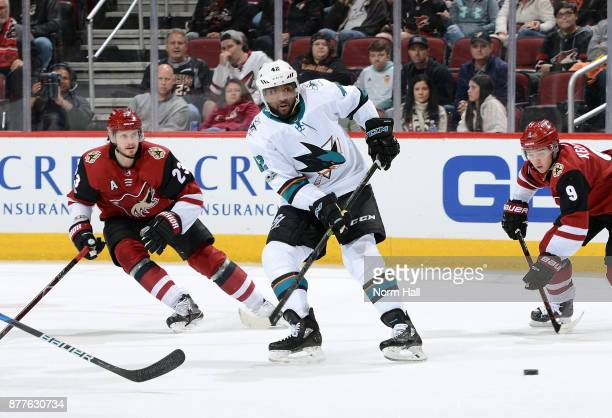 Joel Ward of the San Jose Sharks passes the puck away from Oliver EkmanLarsson and Clayton Keller of the Arizona Coyotes during the second period at...