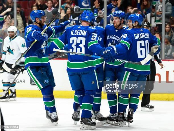 Joel Ward of the San Jose Sharks skates away dejected as Vancouver Canuck players Alexander Edler Henrik Sedin Markus Granlund and Daniel Sedin...