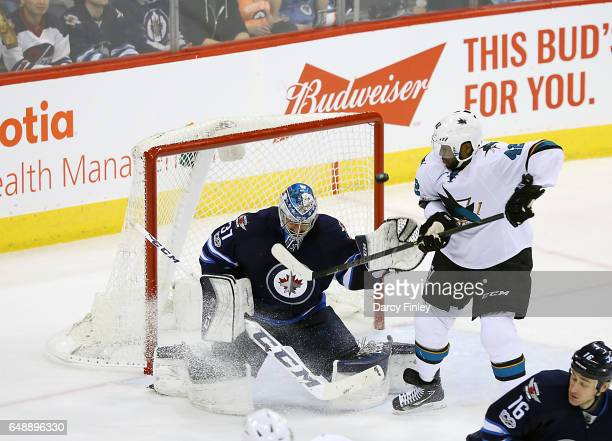 Joel Ward of the San Jose Sharks watches as the puck flies past goaltender Connor Hellebuyck of the Winnipeg Jets and wide of the net during second...
