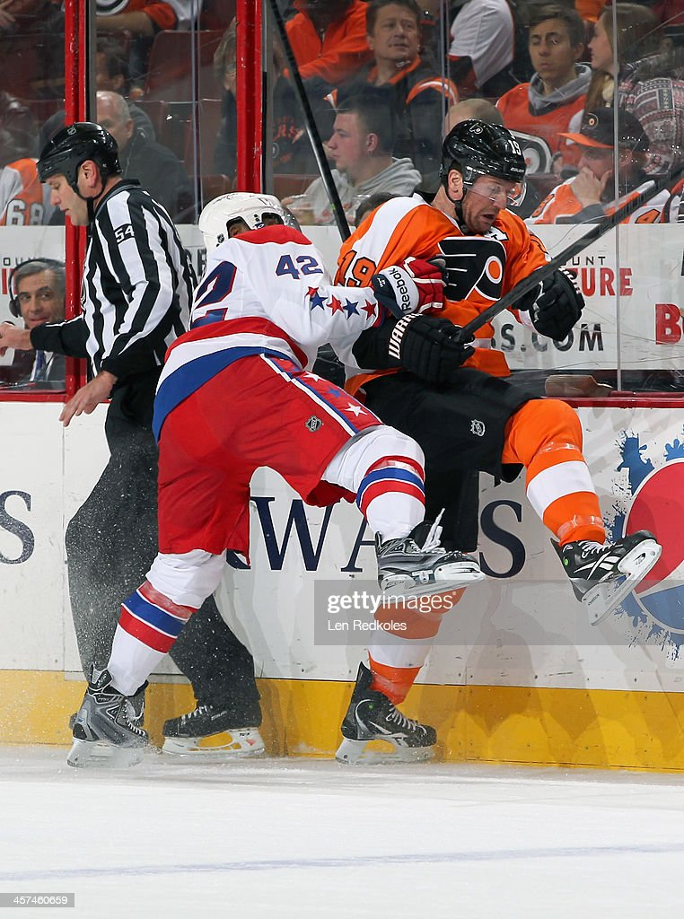 Joel Ward #42 of the Washington Capitals checks Scott Hartnell #19 of the Philadelphia Flyers into the boards on December 17, 2013 at the Wells Fargo Center in Philadelphia, Pennsylvania.
