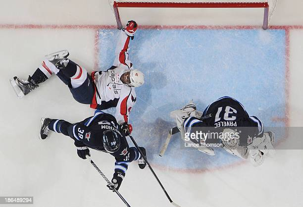 Joel Ward of the Washington Capitals falls to the ice in the crease as Tobias Enstrom and goaltender Ondrej Pavelec of the Winnipeg Jets keep an eye...