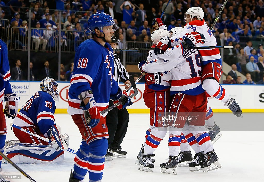 Joel Ward #42 of the Washington Capitals is mobbed by his teamates after scoring the game winning goal at 19:58 as Henrik Lundqvist #30 and J.T. Miller #10 of the New York Rangers look on in Game One of the Eastern Conference Semifinals during the 2015 NHL Stanley Cup Playoffs at Madison Square Garden on April 30, 2015 in New York City. Capitals defeated the Rangers 2-1.