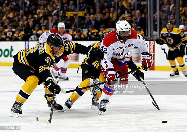 Joel Ward of the Washington Capitals skates to the net as Matt Bartkowski and Johnny Boychuk of the Boston Bruins defend during a game at the TD...