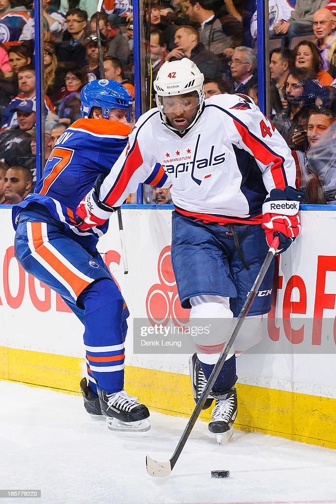 Joel Ward #42 of the Washington Capitals skates with the puck past Anton Belov #77 of the Edmonton Oilers during an NHL game at Rexall Place on October 24, 2013 in Edmonton, Alberta, Canada. The Capitals defeated the Oilers 4-1.