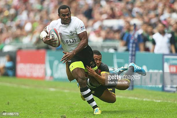 Joeli Lutumailagi of Fiji is tackled by Marcus Watson of England during the Cup semifinal match between England and Fiji during day three of the 2014...