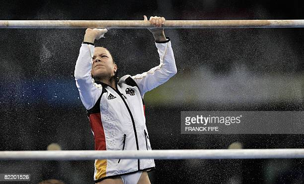 Joeline Moebius of Germany cleans the bars before performing during a practice session of the artistic gymnastics event of the Beijing 2008 Olympic...