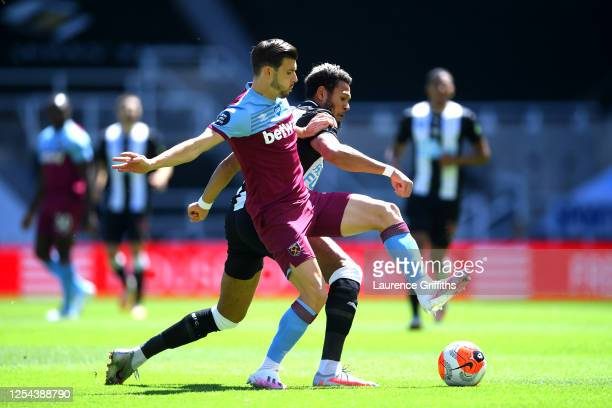 Joelinton is challenged by Aaron Cresswell during the Premier League match between Newcastle United and West Ham United at St James Park on July 05...
