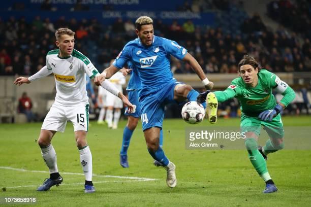 Joelinton of 1899 Hoffenheim is challenged by Jordan Beyer of Borussia Monchengladbach and Yann Sommer of Borussia Monchengladbach during the...