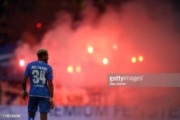 Joelinton of Hoffenheim reacts as fans of Hoffenheim burn flares during the Bundesliga match between 1 FSV Mainz 05 and TSG 1899 Hoffenheim at Opel...