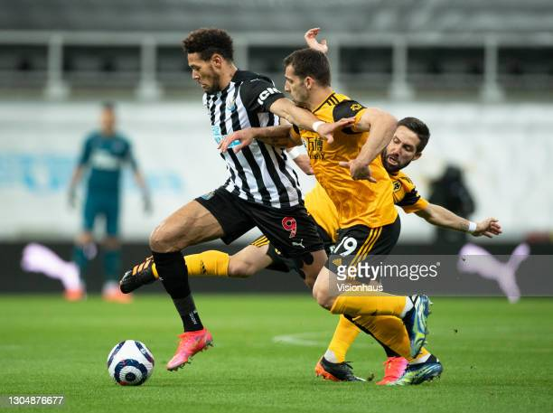 Joelinton of Newcastle United in action with Jonny and João Moutinho of Wolverhampton Wanderers during the Premier League match between Newcastle...