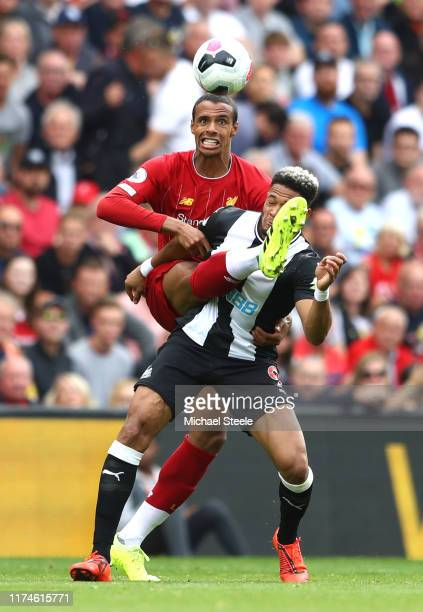 Joelinton of Newcastle United is challenged by Joel Matip of Liverpool during the Premier League match between Liverpool FC and Newcastle United at...