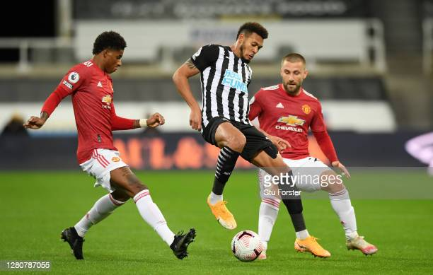 Joelinton of Newcastle United is challenged by Marcus Rashford and Luke Shaw of Manchester United during the Premier League match between Newcastle...
