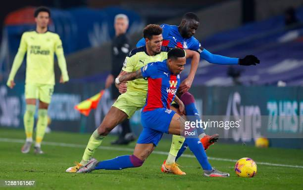 Joelinton of Newcastle United is challenged by Nathaniel Clyne and Cheikhou Kouyate of Crystal Palace during the Premier League match between Crystal...