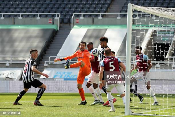 Joelinton of Newcastle United scores their team's second goal under pressure from Lukasz Fabianski of West Ham United during the Premier League match...