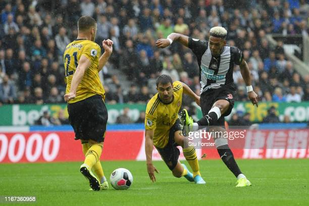 Joelinton of Newcastle United shoots for goal under pressure from Sokratis Papastathopoulos and Calum Chambers of Arsenal during the Premier League...