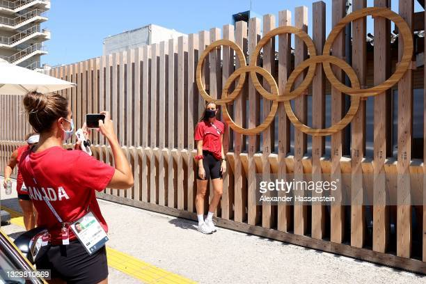 Joelle Bekhazi of Waterpolo Team Canada takes a picture of her team mate Monika Eggens in front of the Olympic Rings at the Olympic Village ahead of...