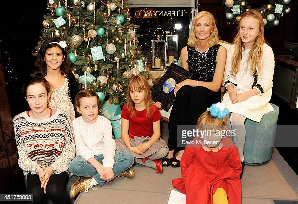 Joely Richardson poses with children as she officially opens the Tiffany Co Christmas Shop on Bond Street London on November 24 2013 in London England