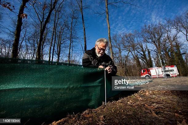 Joerg Dorowski a volunteer of German environment association NABU builds a fence for amphibian migrations on March 3 2012 in Potsdam Germany The so...
