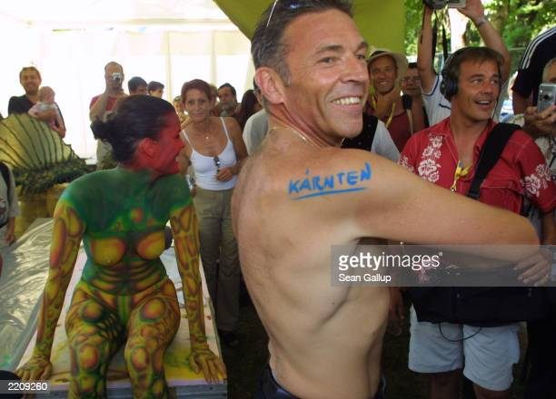Joerg Haider governor of the Austrian state of Carinthia and onagain offagain leader of the Austrian rightwing Freedom Party shows off a painted...