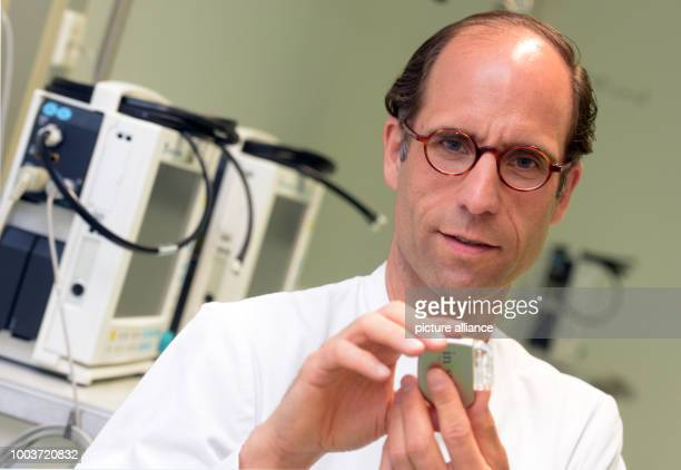 Joerg Lindemann holds up a tongue pacer at the university clinic in Ulm Germany 31 May 2017 Lindemann researches sleep and insomnia Photo Stefan...