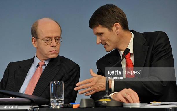 Joerg Schneider, chief financial officer of Munich Re, right, speaks to Nikolaus von Bomhard, chief executive officer of Munich Re, at a news...