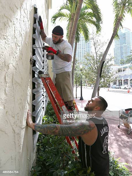 Joe's Stone Crab employees Jordan Garcia top and Manny Cortes installing shuttles in preparation for Tropical Storm Erika on Friday August 28 in...