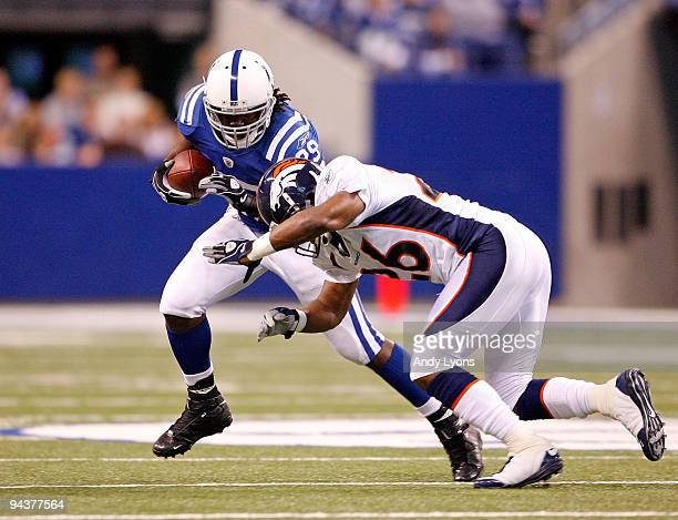 Joesph Addai of the Indianapolis Colts runs the ball against Ty Law of the Denver Broncos during the NFL game at Lucas Oil Stadium on December 13,...