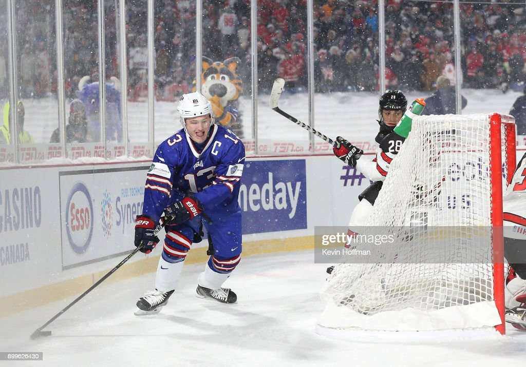 Joey Anderson #13 of United States with the puck behind the net as Victor Mete #28 of Canada pursues during the IIHF World Junior Championship at New Era Field on December 29, 2017 in Buffalo, New York. The United States beat Canada 4-3.