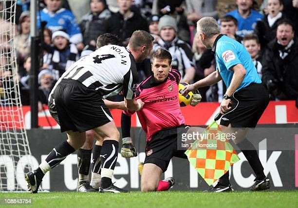 Joey Barton and Kevin Nolan try to get the ball from Arsenal keeper Wojciech Szczesny during the Barclays Premier league match between Newcastle...