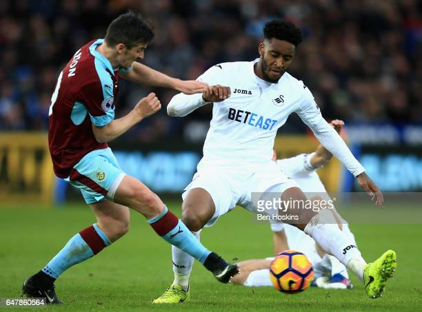 Joey Barton of Burnley and Leroy Fer of Swansea City battle for possession during the Premier League match between Swansea City and Burnley at...