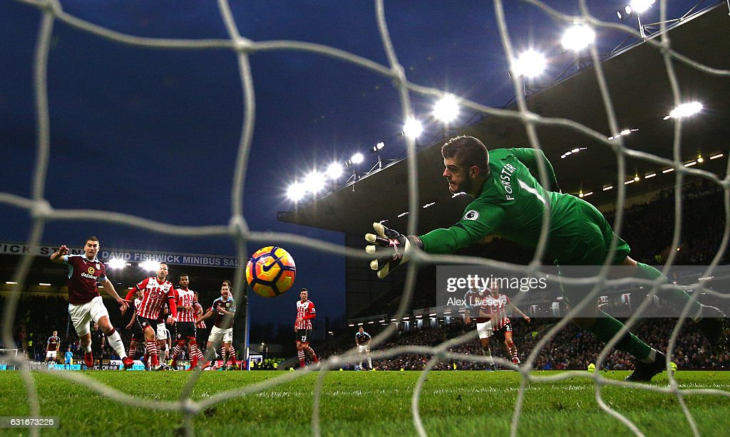 Joey Barton of Burnley scores his sides first goal past Fraser Forster of Southampton (R) during the Premier League match between Burnley and Southampton at Turf Moor on January 14, 2017 in Burnley, England.