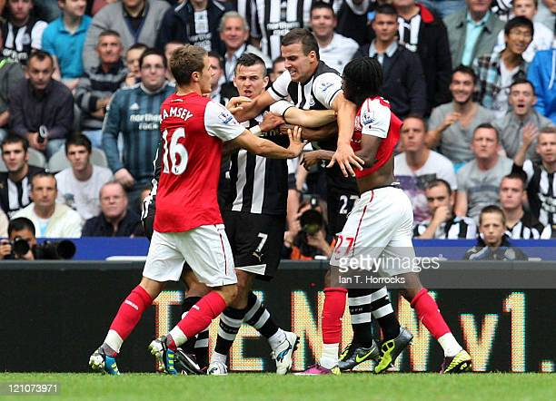Joey Barton of Newcastle grapples with Gervinho of Arsenal during the Barclays Premier League game between Newcastle United and Arsenal at St James'...