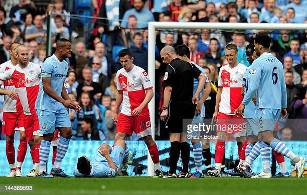 Joey Barton of QPR clashes with Sergio Aguero of Manchester City after being shown the red card by Referee Mike Dean during the Barclays Premier...