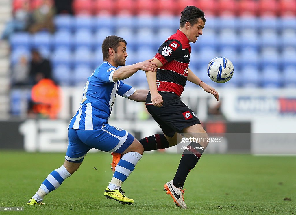 Joey Barton of Queens Park Rangers shields the ball from Shaun Maloney of Wigan Athletic during the Sky Bet Championship Play Off Semi Final first leg match between Wigan Athletic and Queens Park Rangers at DW Stadium on May 9, 2014 in Wigan, England.