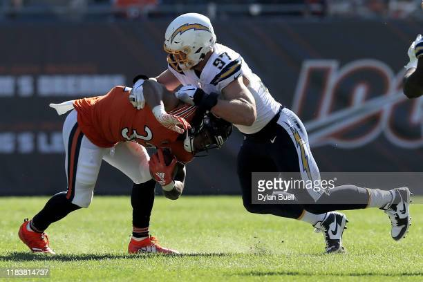 Joey Bosa of the Los Angeles Chargers tackles David Montgomery of the Chicago Bears in the second quarter at Soldier Field on October 27, 2019 in...