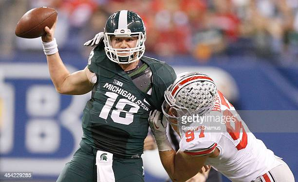 Joey Bosa of the Ohio State Buckeyes drags down Connor Cook of the Michigan State Spartans in the third quarter during the Big 10 Conference...