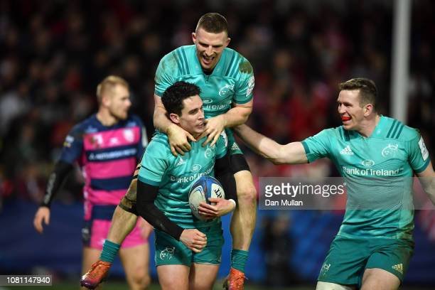 Joey Carbery of Munster celebrates with team mates Andrew Conway and Chris Farrell after scoring a try during the Champions Cup match between...