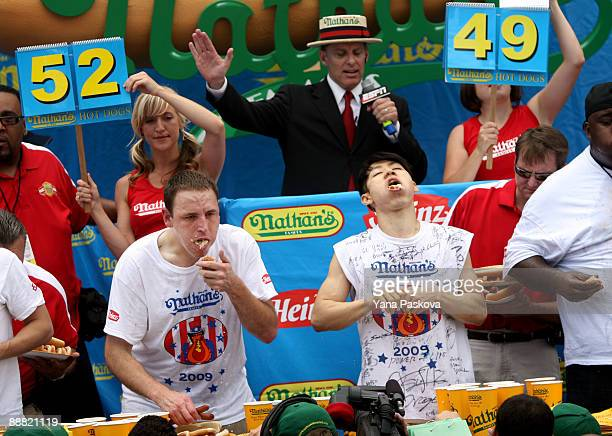 Joey Chestnut of San Jose California and Takeru Kobayashi of Nagano Japan stuff hot dogs into their mouths during Nathan's Famous Fourth of July hot...