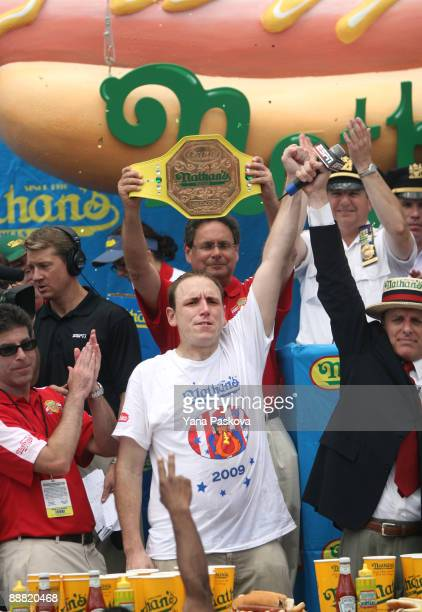 Joey Chestnut of San Jose California raises hands in victory with Chairman of Major League Eating George Shea after defeating Takeru Kobayashi of...