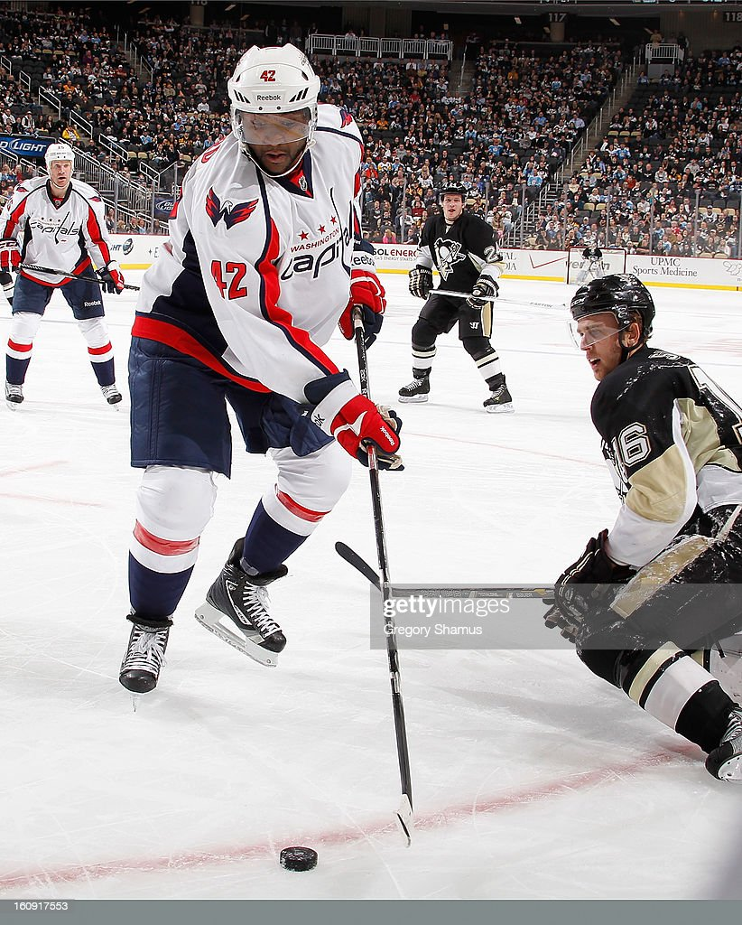 Joey Crabb #15 of the Washington Capitals reaches for the loose puck in front of Brandon Sutter #16 of the Pittsburgh Penguins on February 7, 2013 at Consol Energy Center in Pittsburgh, Pennsylvania.
