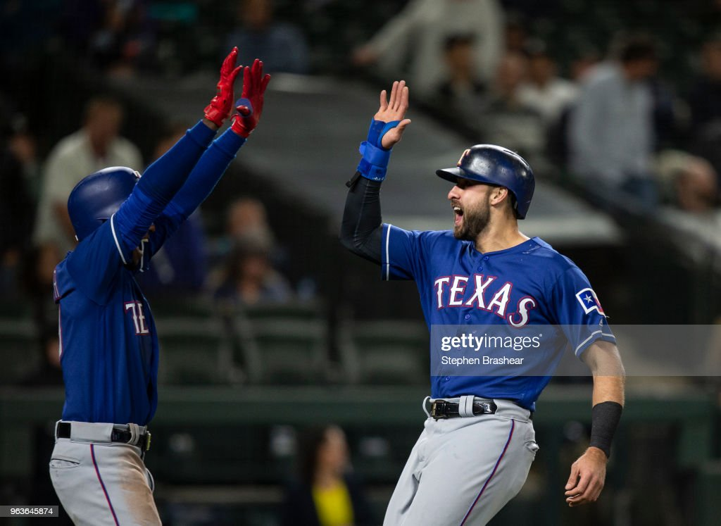 Joey Gallo #13 (R) and Jurickson Profar #19 of the Texas Rangers celebrate after scoring on a three-run double by Rougned Odor #12 off of relief pitcher Edwin Diaz #39 of the Seattle Mariners during the ninth inning of a game at Safeco Field on May 29, 2018 in Seattle, Washington.
