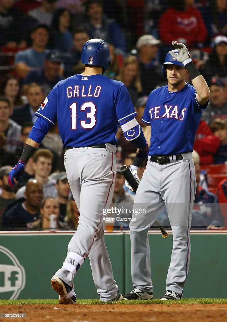 Joey Gallo #13 high fives Jared Hoying #31 of the Texas Rangers after hitting a solo home run in the eighth inning of a game against the Boston Red Sox at Fenway Park on May 23, 2017 in Boston, Massachusetts.