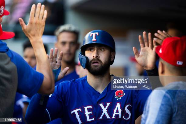 Joey Gallo of the Texas Rangers highfives teammates in the dugout after scoring on a double by Logan Forsythe of the Texas Rangers in the fourth...