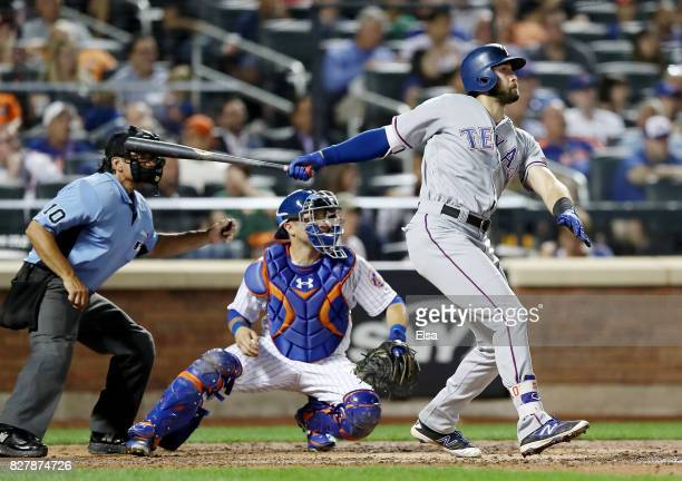 Joey Gallo of the Texas Rangers hits an RBI double as Travis d'Arnaud of the New York Mets defends in the sixth inning during interleague play on...