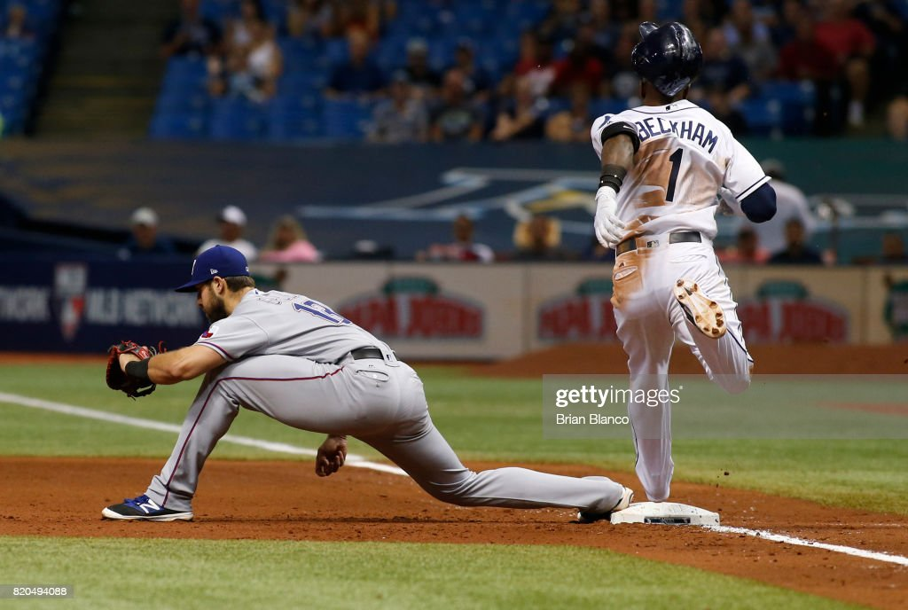 Joey Gallo #13 of the Texas Rangers reaches to get the out at first base after Tim Beckham #1 of the Tampa Bay Rays grounded out to second baseman Rougned Odor to end the fourth inning of a game on July 21, 2017 at Tropicana Field in St. Petersburg, Florida.