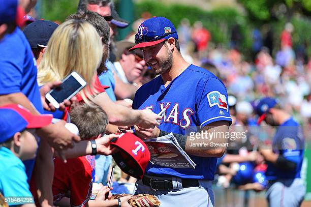 Joey Gallo of the Texas Rangers signs autographs for fans prior to the spring training game against the Los Angeles Angels at Tempe Diablo Stadium on...