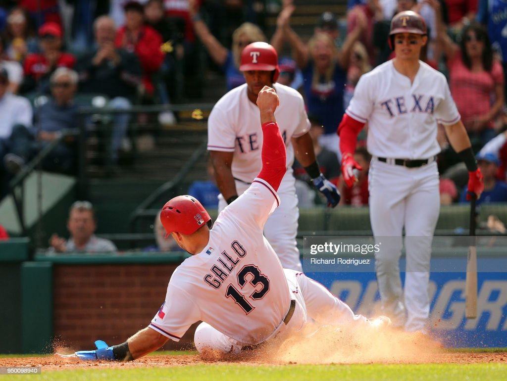 Joey Gallo #13 of the Texas Rangers slides home after he and Adrian Beltre of the Texas Rangers scored on a double in the eigth inning agains the Seattle Mariners at Globe Life Park in Arlington on April 22, 2018 in Arlington, Texas.