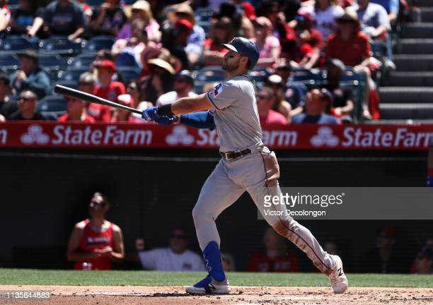 Joey Gallo of the Texas Rangers watches his hit to right field go for a tworun homerun in the second inning during the MLB game against the Los...